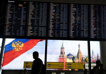 Passengers walk past a departure board at Sheremetyevo international airport in Moscow, Russia, Monday, July 8, 2019.