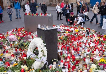 People place down flowers and candles at the marketplace in the old town of Halle, Germany, October 11, 2019.