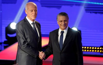Nabil Karoui and Kais Saied shake hands before a televised debate in Tunis, Tunisia, October 11, 2019.