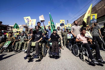 Fighters and veterans from the Kurdish women's protection units (YPJ) and the people's protection units (YPG) march in front of the UN headquarters in Qamishli, on October 8, 2019.