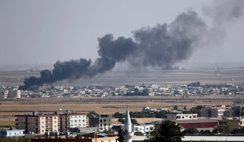 Smoke billows out after Turkish shelling on the Syrian town of Ras al Ain, as seen from the Turkish border town of Ceylanpinar, Turkey, October 13, 2019.