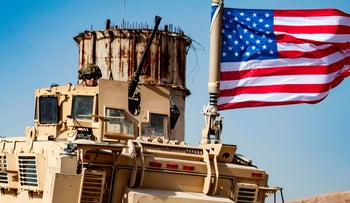 U.S. soldier sits atop an armored vehicle during a demonstration by Syrian Kurds on the outskirts of Ras al-Ayn, Syria, October 6, 2019.