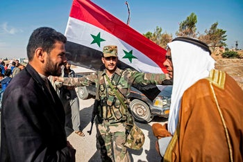 Locals welcome Syrian regime forces as they arrive at the western entrance of the town of Tel Tamer in the countryside of Syria's northeastern Hasakeh province, October 14, 2019.