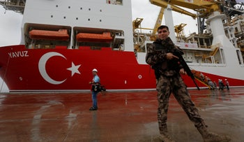 A Turkish police officer patrols the dock next to the drilling ship 'Yavuz' to be dispatched for operations in an area off the Karpas peninsula on Cyprus' east coast in August 2019.