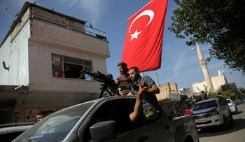 Turkish-backed Syrian rebels drive on a street in the Turkish border town of Akcakale in Sanliurfa province, Turkey, October 14, 2019.