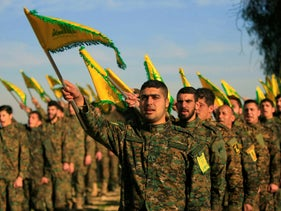 Hezbollah fighters hold flags as they attend the memorial of their slain leader Sheik Abbas al-Mousawi on February 13, 2016.