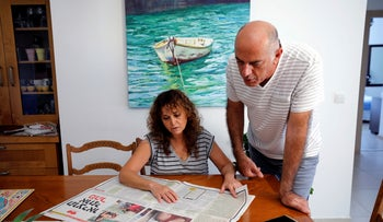 the uncle of Naama Issachar, and his wife look at a newspaper with an article about Naama at their home in Rehovot, Israel October 13, 2019.