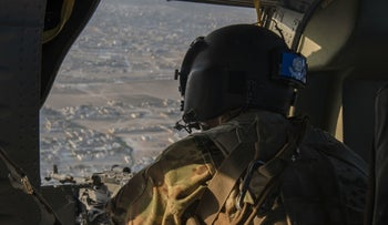 A UH-60 Black Hawk crew member flies over the Syrian countryside, August 17, 2019.