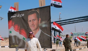 """A man passing a poster of Syrian President Bashar Assad at the newly opened crossing between the Iraqi town of Qaim and Syria's Boukamal, September 30, 2019. The Arabic sign reads, """"Congratulations victory."""""""
