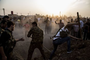 Syrians burying Syrian Democratic Forces fighters killed fighting Turkish advance in the Syrian town of Qamishli, October 12, 2019.