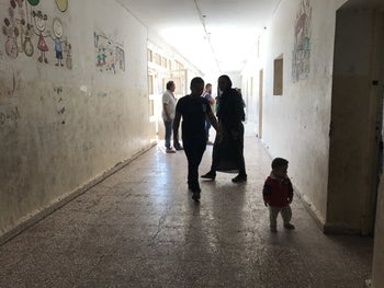 People walking down the corridor of a school turned into a temporary shelter in Hasaka, Syria, October 2019.