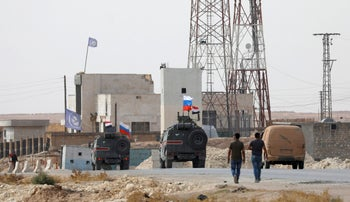 Russian and Syrian national flags flutter on military vehicles near Manbij, Syria October 15, 2019.