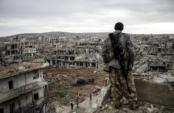 A Kurdish marksman stands atop a building as he looks at the destroyed Syrian town of Kobani, 2015.