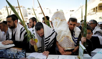 Jewish worshippers hold the Four Species, used in rituals for the holiday of Sukkot, as they pray before a priestly blessing at the Western Wall in Jerusalem's Old City, October 16, 2019.