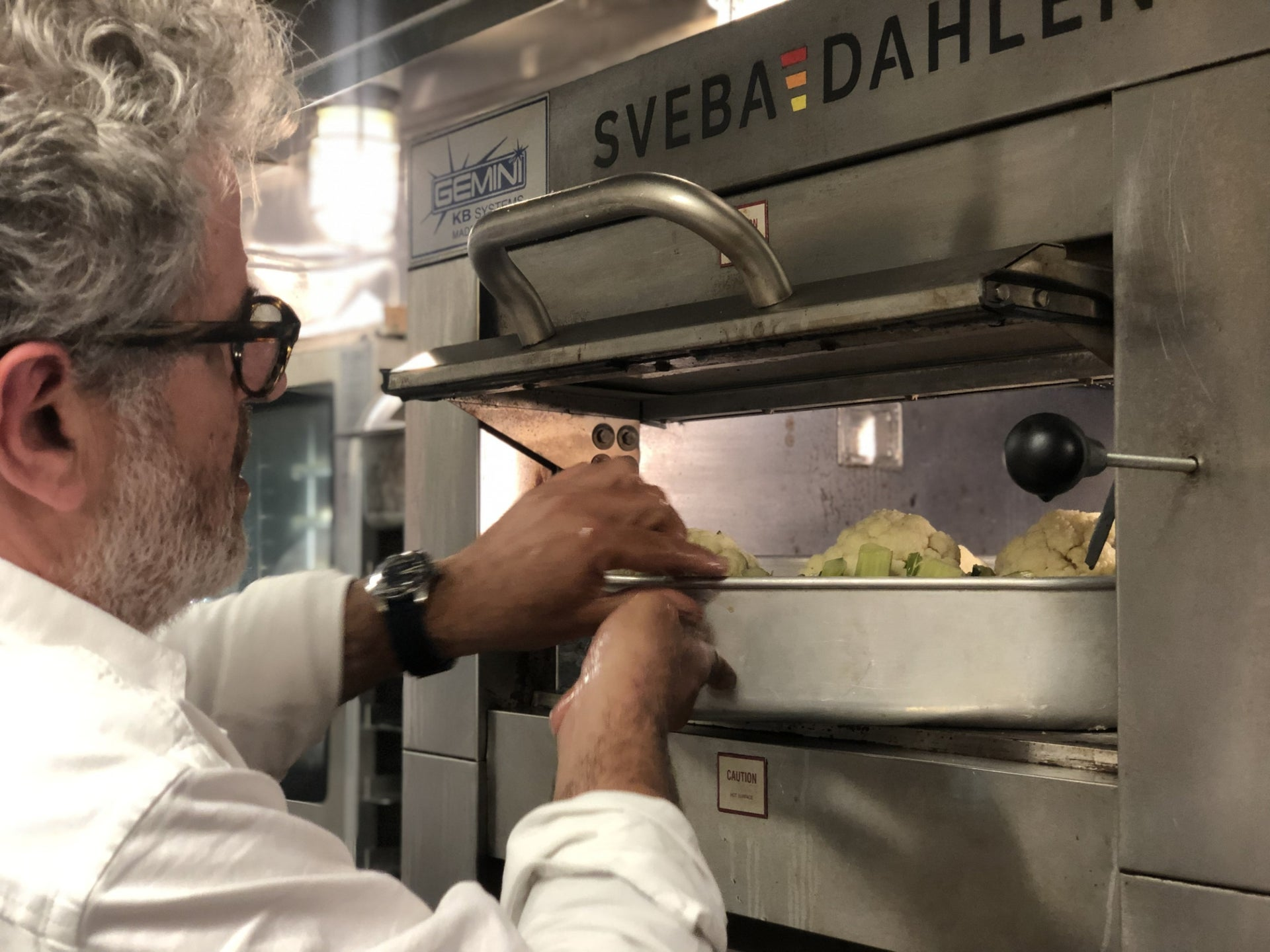 Eyal Shani puts cauliflower into the oven at Miznon North in New York.