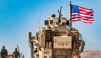 In this file photo taken on October 6, 2019 a US soldier sits atop an armoured vehicle during a demonstration by Syrian Kurds against Turkish threats next to a base for the US-led international coalition on the outskirts of Ras al-Ain town in Syria's Hasakeh province near the Turkish border