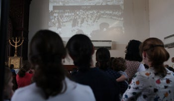 Women watching men attending a cultural event on a screen in the city of Beit Shemesh, Israel, October 2019