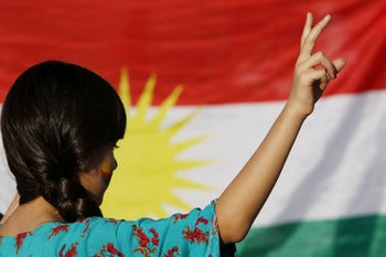 Protester gestures in front of a Kurdish flag during a rally against the Turkish military operation in Syria, in Berlin, Germany, October 14, 2019