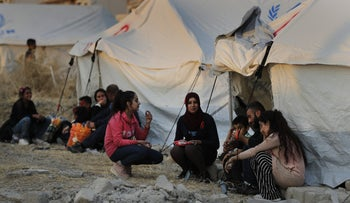 Syrians who were displaced by the Turkish military operation in northeastern Syria wait to receive tents and aid supplies at the Bardarash refugee camp, north of Mosul, Iraq, October 17, 2019.