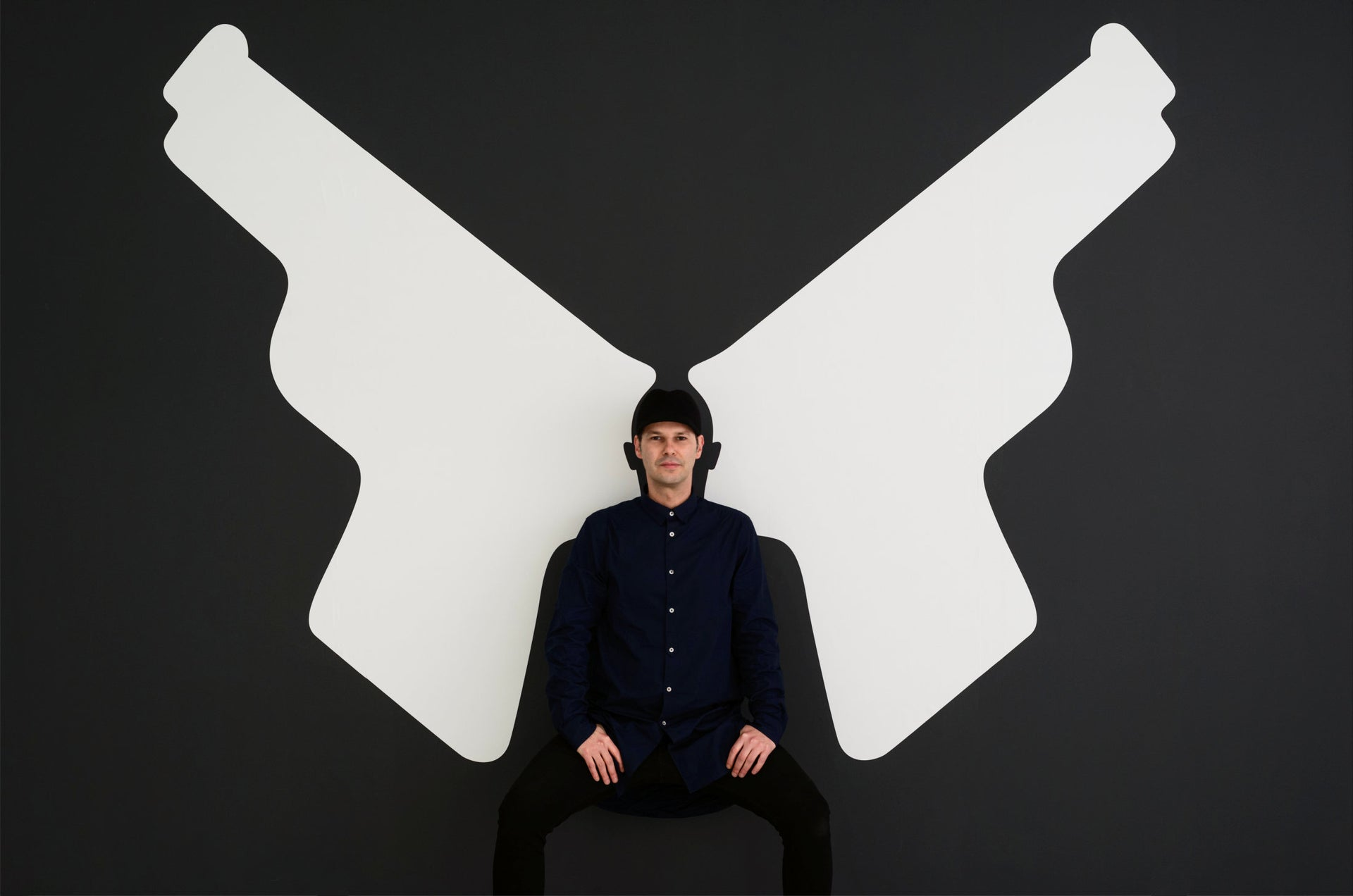 Noma Bar sitting in front of one of his exhibition pieces, London, 2013