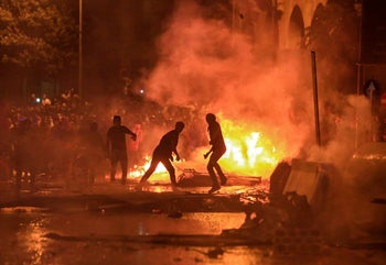 Lebanese demonstrators stand by a fire a make-shift barricade amidst clashes with security forces during a mass protest at Riad al-Solh Square in the center of the capital Beirut on October 18, 2019.