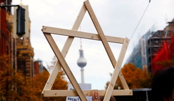 A man carries a wooden Star of David as people attend a demonstration to protest against antisemitism, racism and nationalism in Berlin, Germany, October 13, 2019.