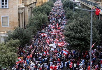 Demonstrators carry national flags and banners during an anti-government protest in downtown Beirut, Lebanon October 20, 2019.