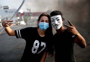 An anti-government couple protesters flash victory signs, as they block a highway that links to north Lebanon in east Beirut, October 20, 2019.