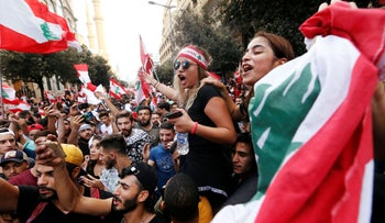 Demonstrators hold national flags during an anti-government protest in downtown Beirut, October 20, 2019.