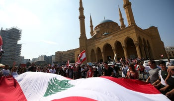 Demonstrators hold a Lebanese flag during an anti-government protest in downtown Beirut, October 21, 2019.