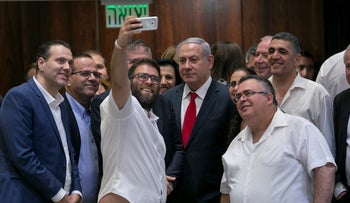 Prime Minister Benjamin Netanyahu posing for a selfie with coalition members after his government passed the nation-state law, July 19, 2018.