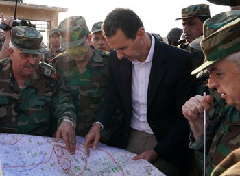 A handout picture released by the Syrian Presidency on October 21, 2019, shows Assad and army officers in al-Habit on the southern edges of the Idlib province.