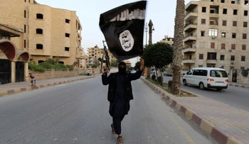 A member loyal to the Islamic State group waving an ISIS flag in Raqqa, June 2014.