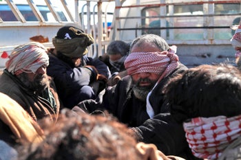 Alleged Islamic State fighters sit blindfolded in the back of a pickup truck after being taken into custody by Kurdish forces in eastern Syria, January 30, 2019.