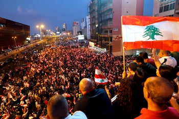 Demonstrators carry national flags during an anti-government protest along a highway in Jal el-Dib, Lebanon, October 21, 2019.