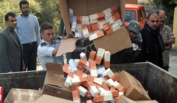 Palestinian customs officials dump Dead Sea beauty products into dumpsters as part of a boycott of goods made in Israeli settlements in the West Bank city of Jericho, on December 16, 2009.