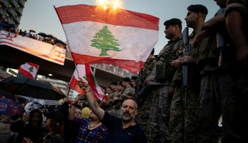 A demonstrator waves a Lebanese national flag next to Lebanese army soldiers during ongoing anti-government protests at a highway in Jal el-Dib, Lebanon, October 23, 2019.