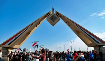Anti-government protesters cross the bridge leading to the Green Zone during a demonstration in central Baghdad, Iraq, October 25, 2019