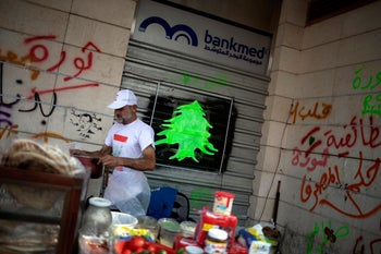 A street vendor is seen outside a closed Bankmed branch in downtown Beirut, Lebanon, October 25, 2019.