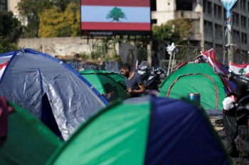 Anti-government protesters block the main highway linking east and west Beirut by tents, stones and bricks during a protest in Beirut, Lebanon, Friday, October 25, 2019.