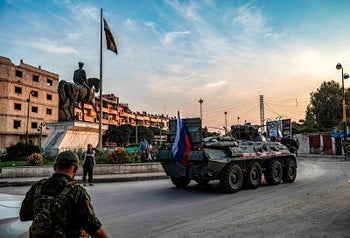 Russian military police vehicles drive past an equestrian statue of Bassel al-Assad, the late brother of President Bashar al-Assad, in the northeastern Syrian city of Qamishli on October 24, 2019.