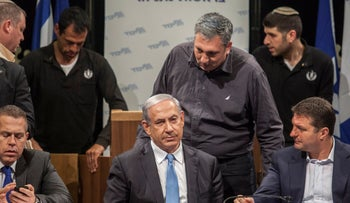 Nir Heftez, standing, talks to Binyamin Netanyahu during a Likud meeting, Tel Aviv, January 25, 2015
