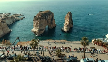 An aerial view shows Lebanese protesters holding hands to form a human chain along the coast from north to south as a symbol of unity during ongoing anti-government demonstrations, on the seaside promenade in the capital Beirut on October 27, 2019. -
