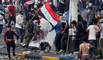 Iraq security forces fire tear gas to disperse anti-government protesters during a demonstration in Baghdad,  Oct. 28, 2019.