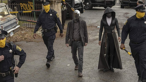 """A scene from """"Watchmen."""" The cops cover their faces using a cloth with a Pantone hue that can only be described as """"Watchmen Yellow."""""""