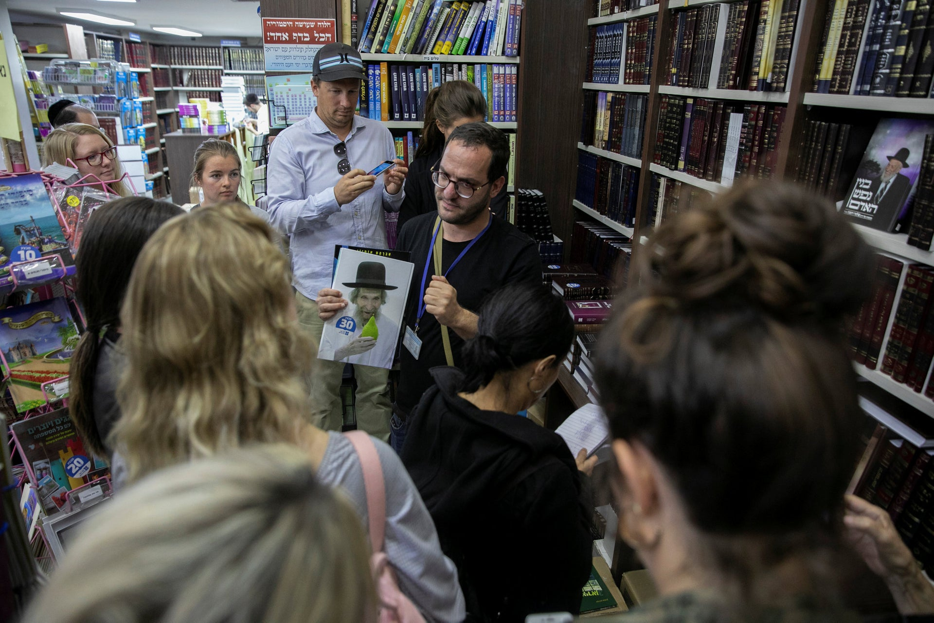Moty Barlev talking to members of his tour in a Jerusalem bookstore. Although most of the books are religious, there are also some novels and comic books written by ultra-Orthodox authors.