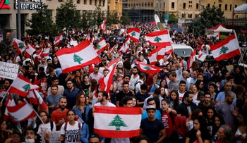 Anti-government protesters chant slogans against the Lebanese government as they hold Lebanese flags, during a protest in Beirut, Lebanon, October 26, 2019.