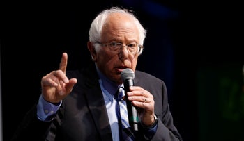 "Democratic presidential candidate Sen. Bernie Sanders speaks at the J Street National Conference, with the hosts of ""Pod Save the World,"" October 28, 2019."