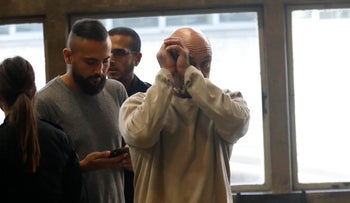 A suspect covers his face at the hearing to extend the detention of the 15 suspects at the Tel Aviv Magistrate's Court, October 29, 2019.