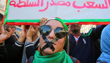 A demonstrator with tapes over her mouth takes part in a protest against the country's ruling elite and to demand an end to corruption and the army's withdrawal from politics in Algiers, Algeria October 29, 2019.